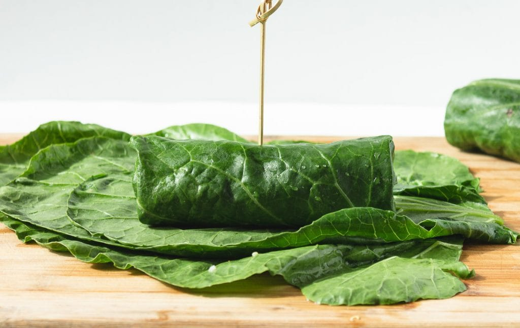 Collard wrap rolled up with a stick through it.