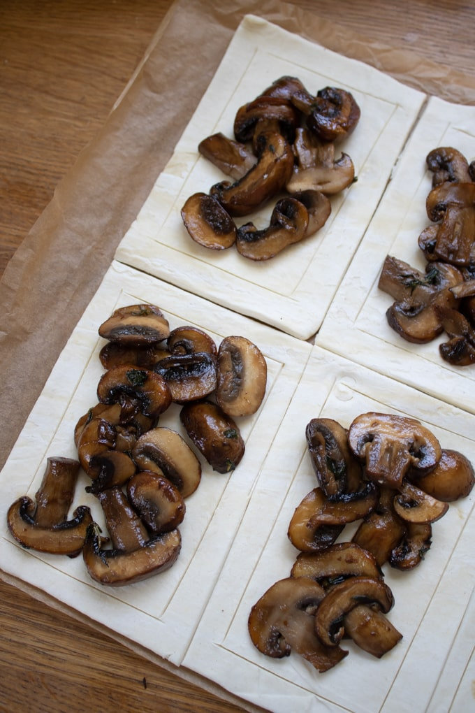 Piling mushrooms onto pastry rectangles.