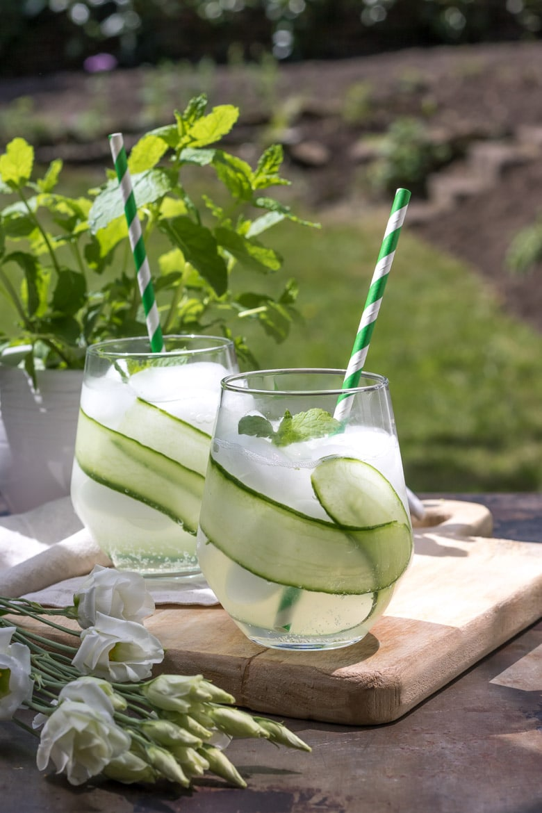 Two glasses filled with ice, cucumber strips and cocktail.