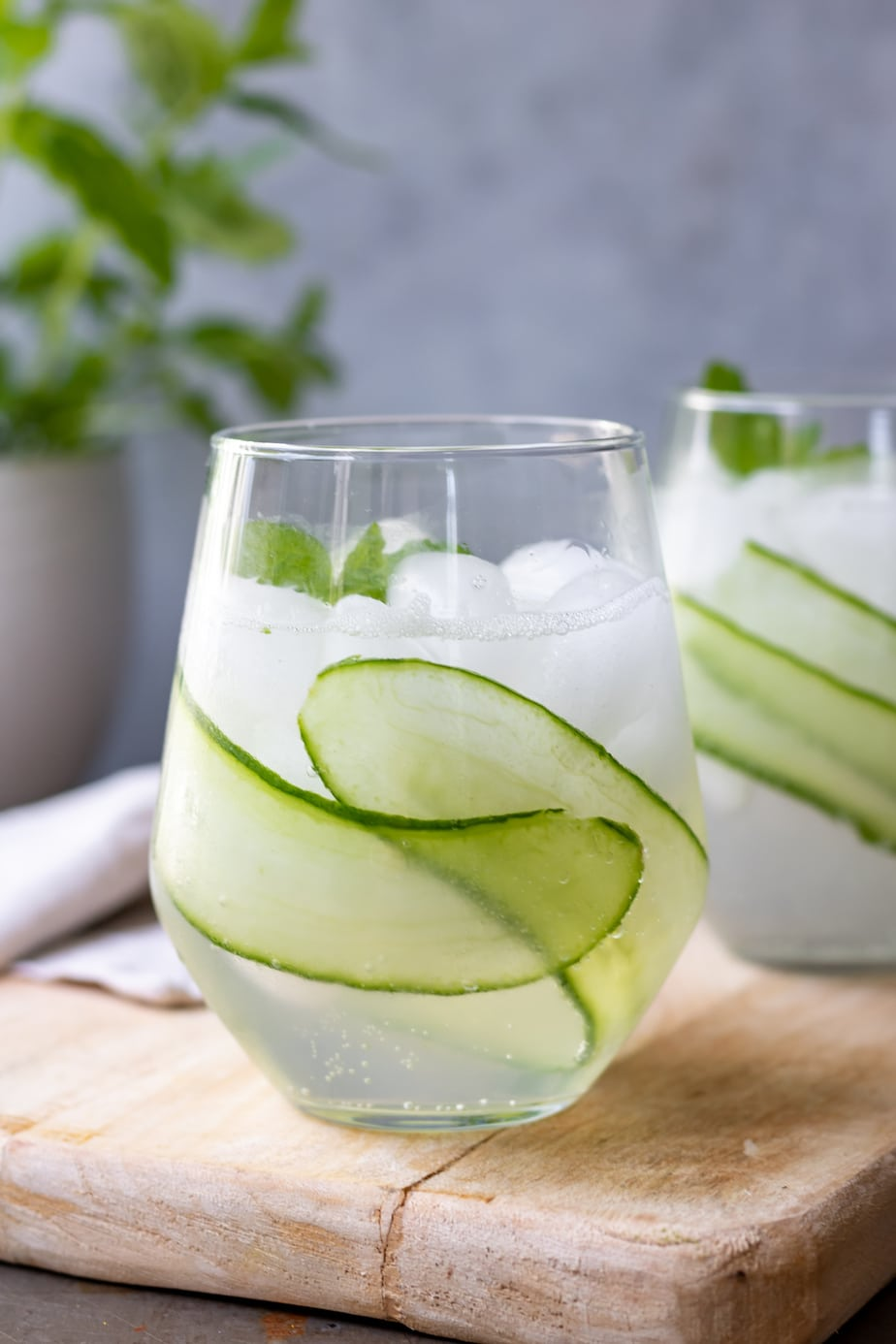 Glass of cocktail with ice and slices of cucumber.