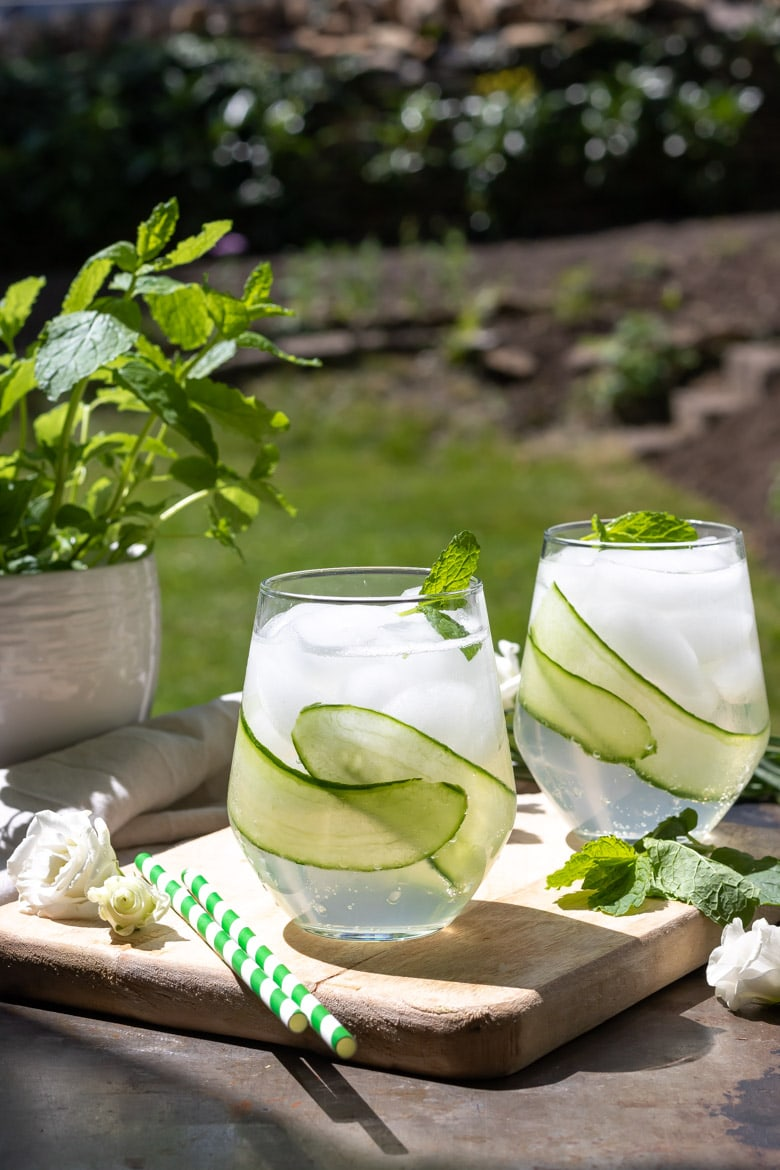 Glasses of cocktails outside, with cucumber ribbons.