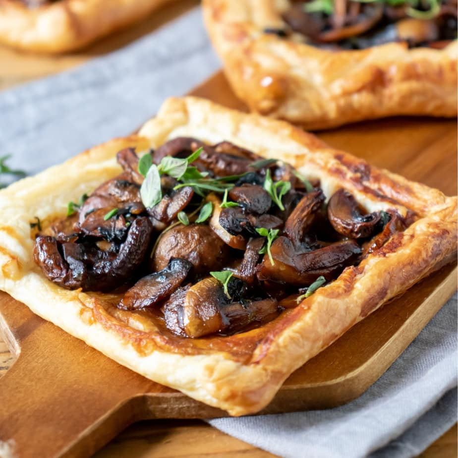 Mushroom tarts on a wooden board.