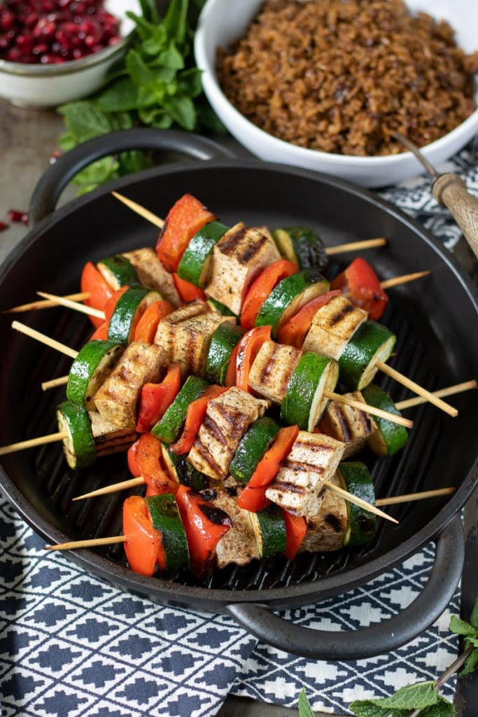 Vegetable tofu skewers piled on a grill pan.