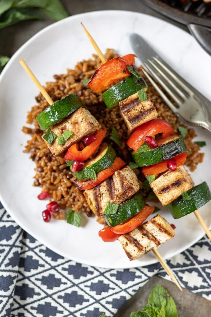 Tofu skewers on rice and grains.