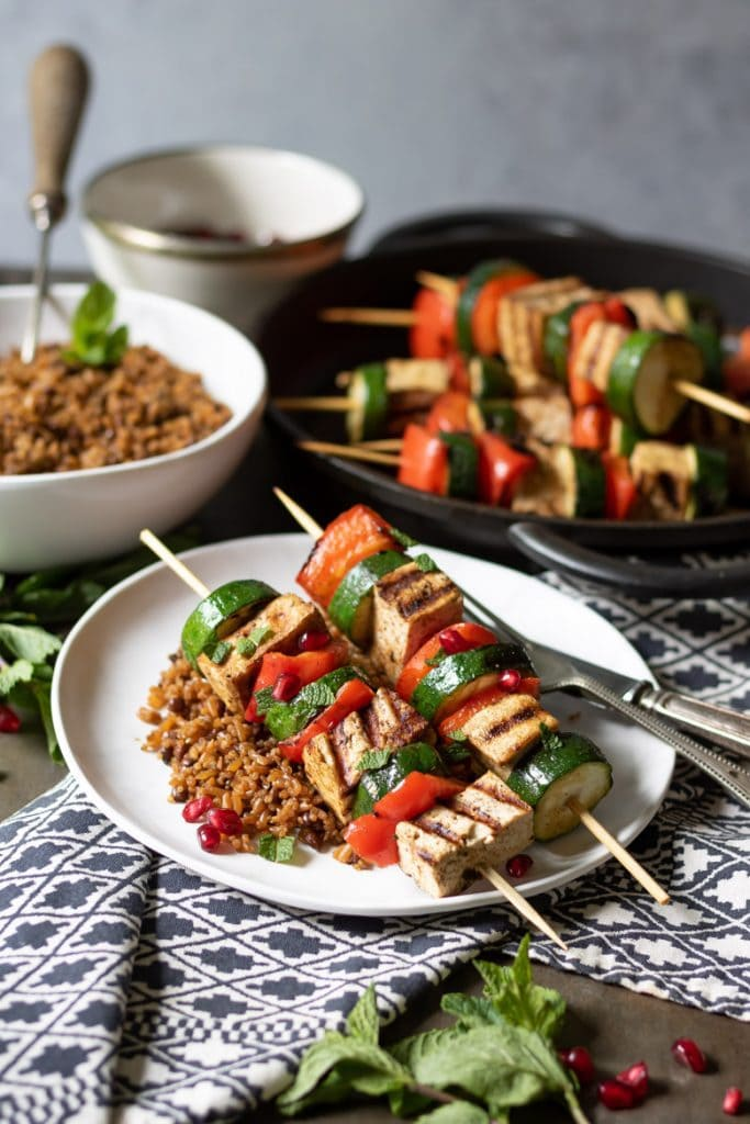 Vegetable tofu skewers on a plate with rice.