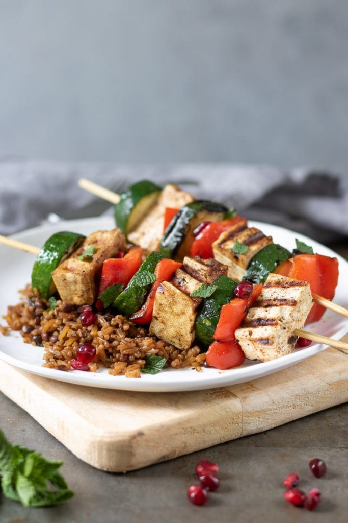 Tofu veg skewers on a plate with rice and pomegranate seeds.