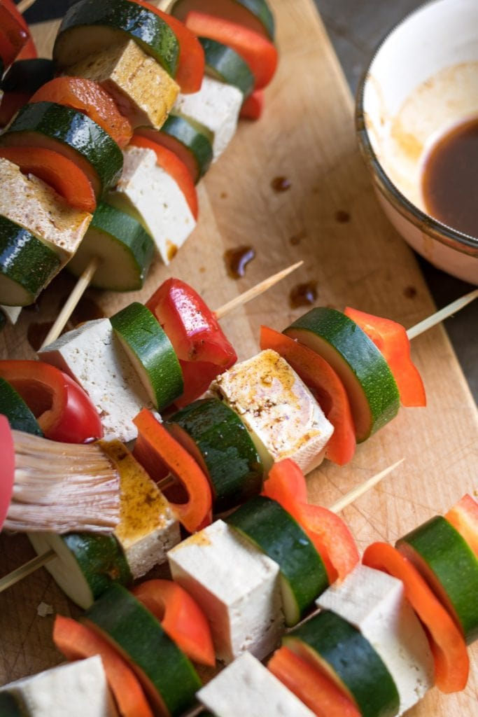Brushing marinade on tofu veggie kabobs.