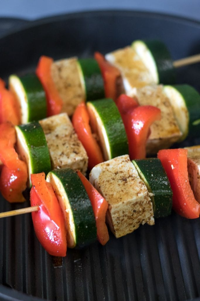 Close up of tofu veg skewers cooking.