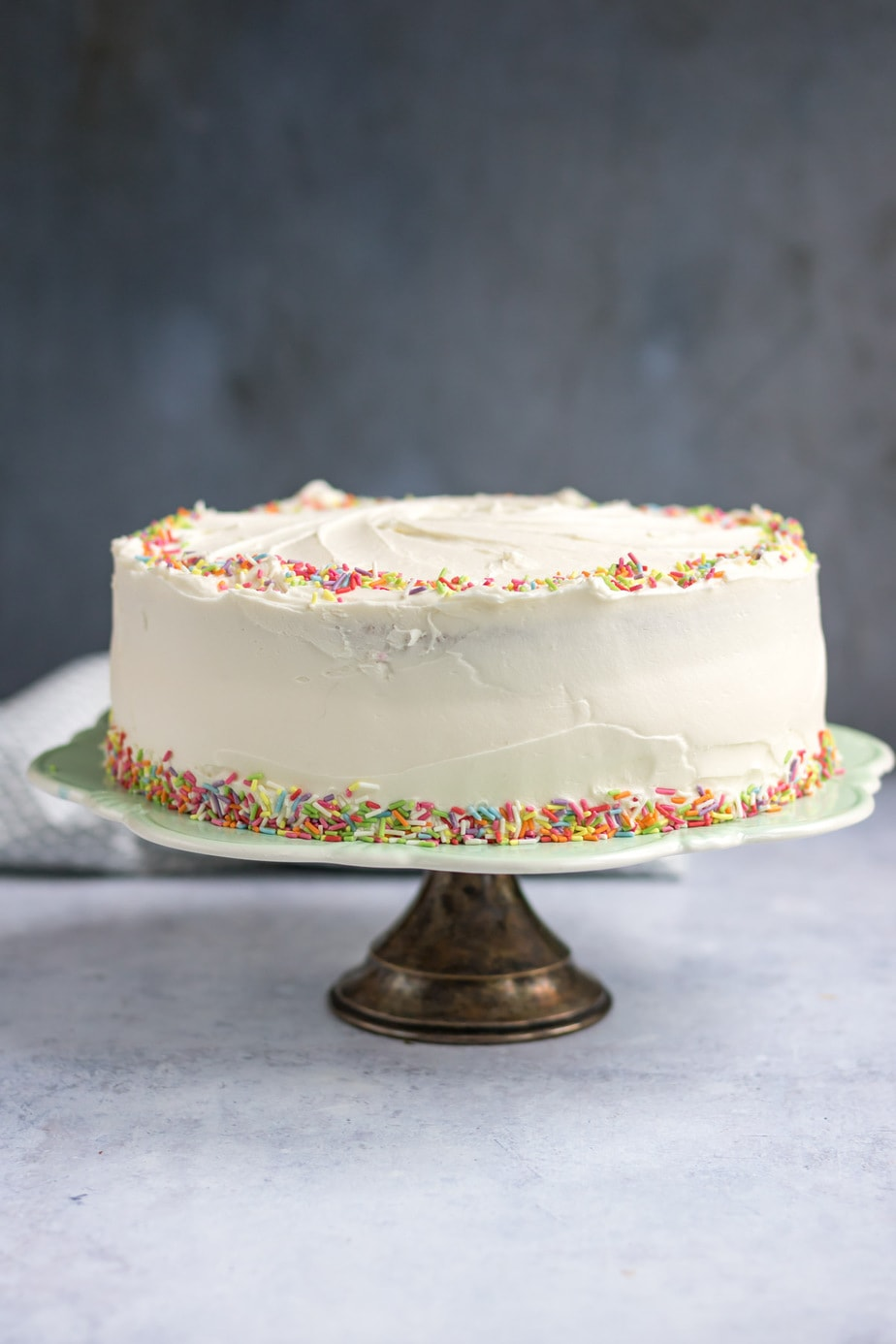 Layer cake with frosting and sprinkles on a cake stand.