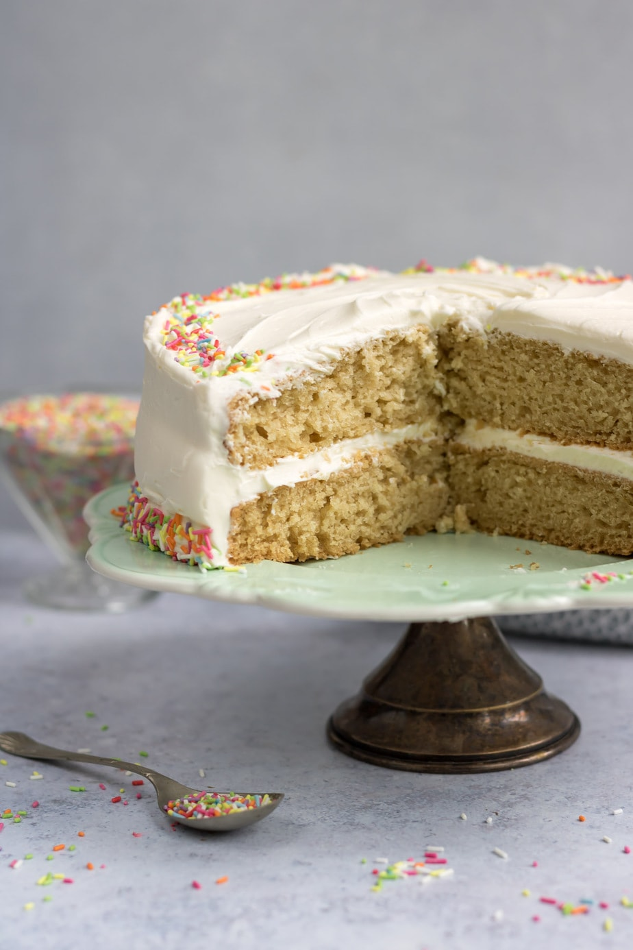 Vegan layer cake with slices removed, on a cake stand