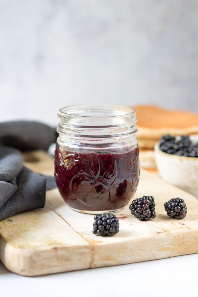 jar of blackberry compote on a wooden board.