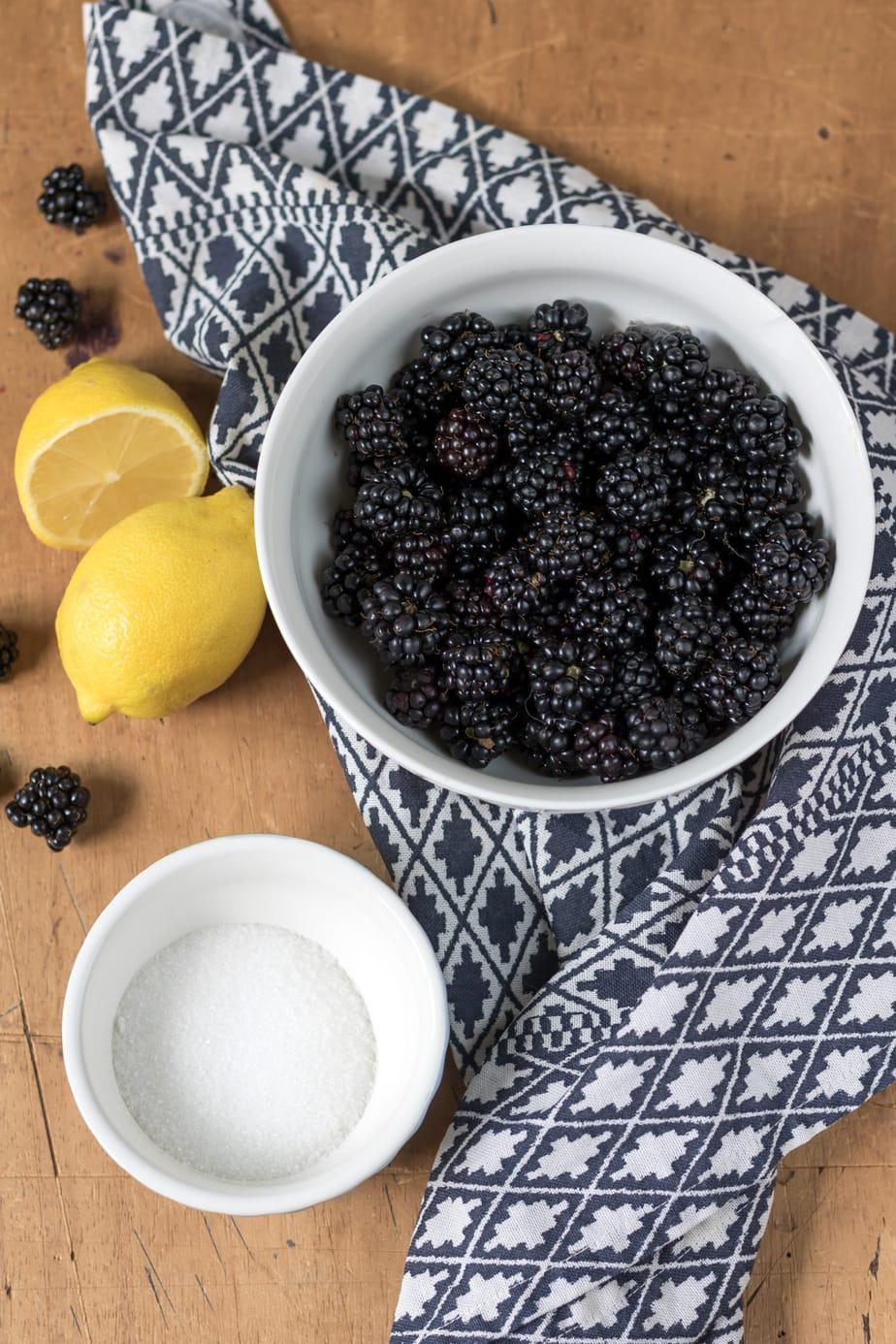 Table with blackberries, lemons and sugar.