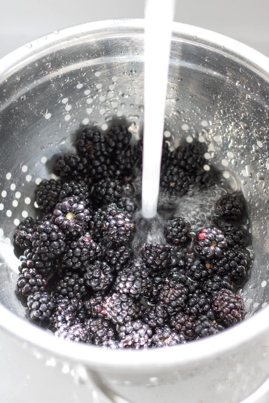 Blackberries being washed in a colander.