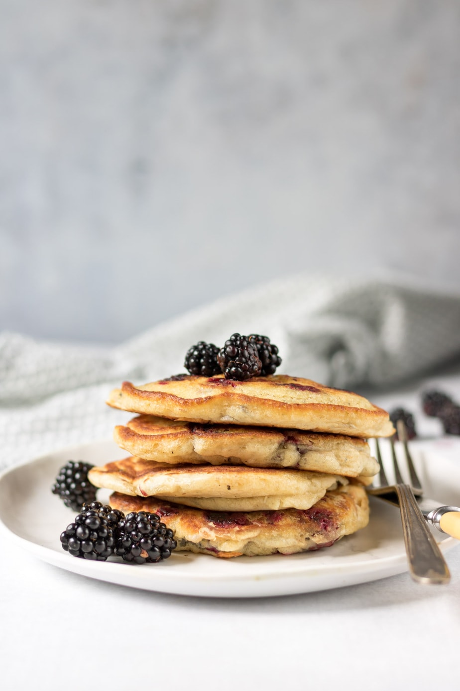 Stack of pancakes with blackberries on top.