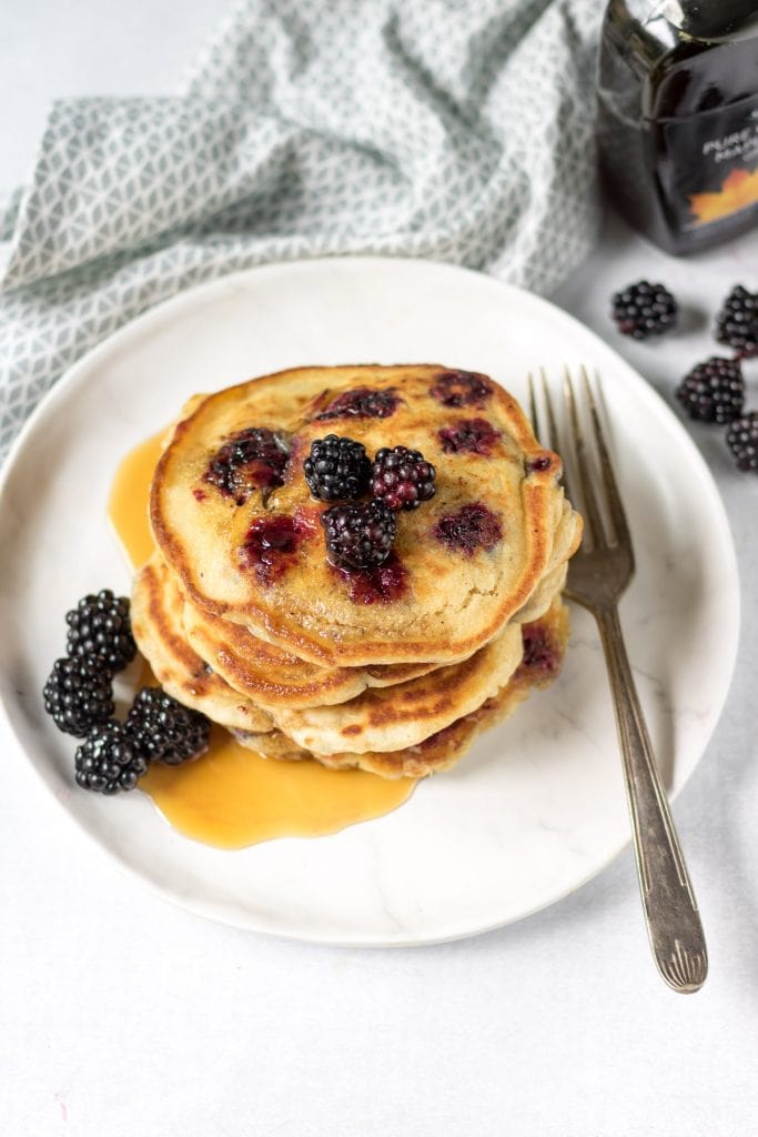 Stack of blackberry pancakes with syrup.