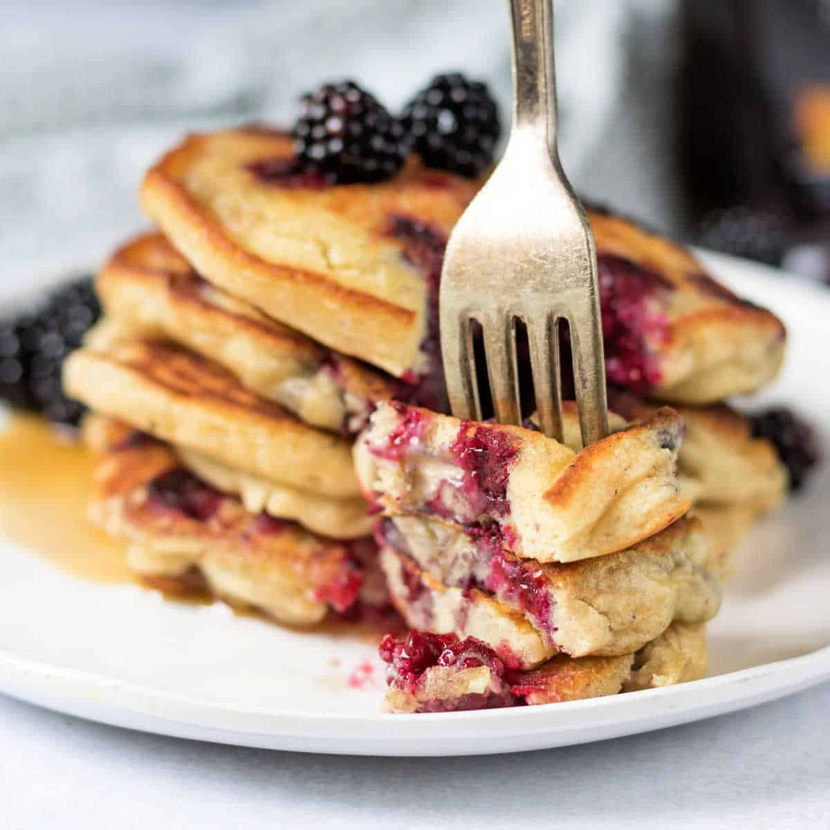 Stack of pancakes with blackberries and a fork in a piece..