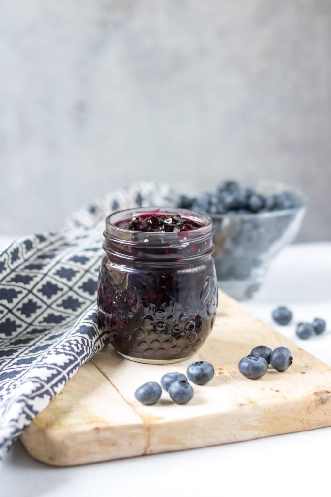Jar of blueberry compote on a wooden board.