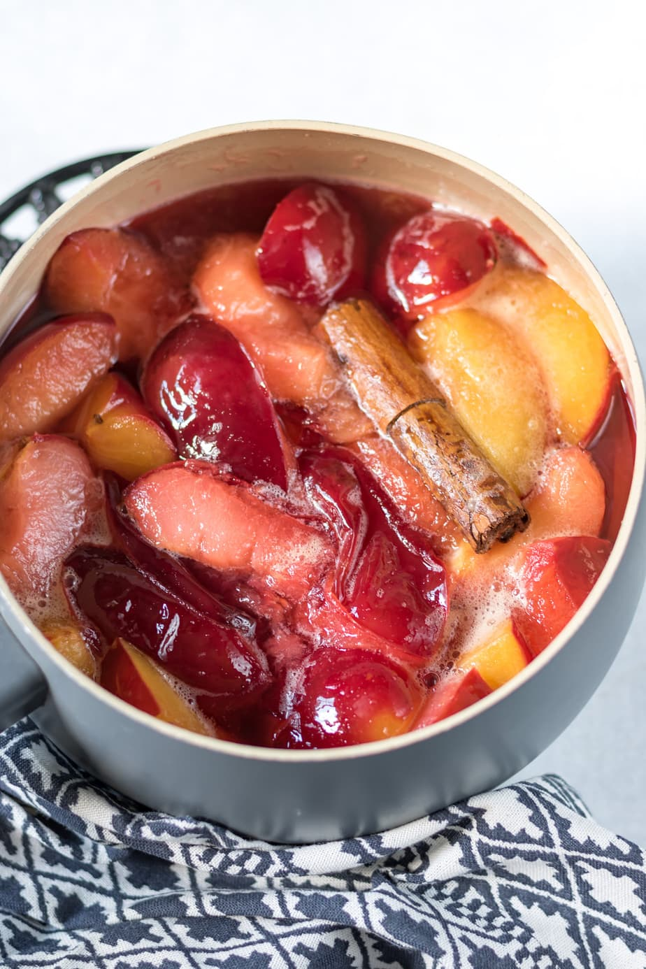 Pot of cooked plums with cinnamon stick.
