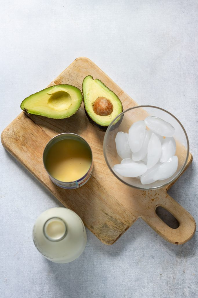 Avocado, condensed milk, ice and milk on a wooden board.