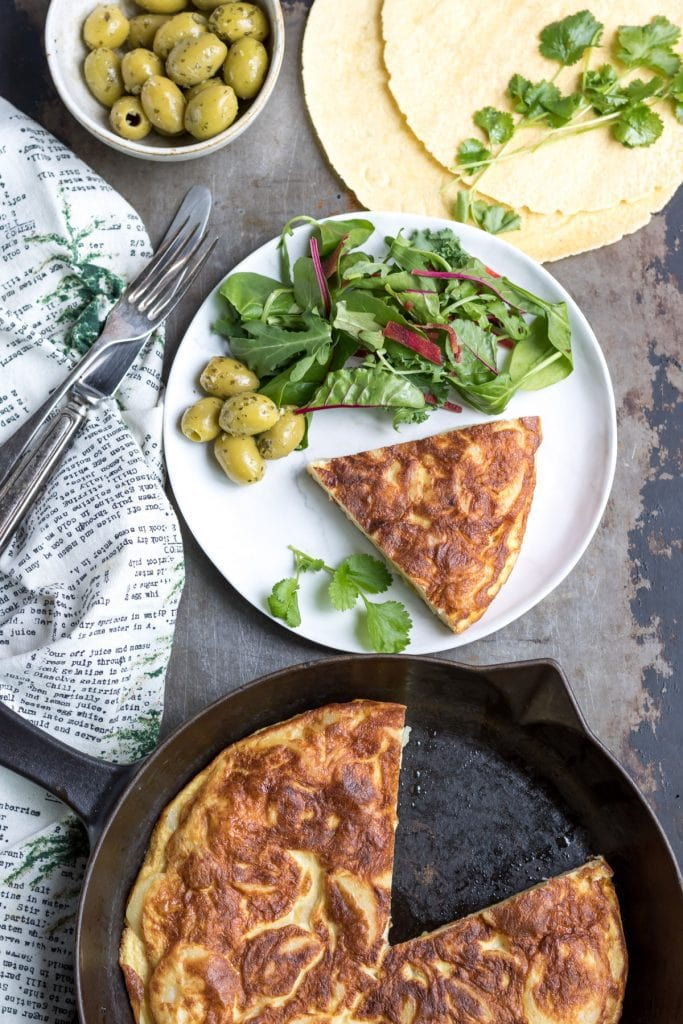 Skillet with Spanish Omelette with a piece taken out.