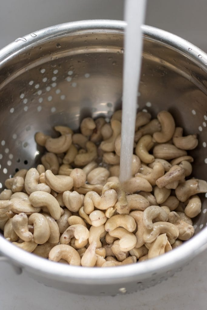 Rinsing cashews in a colander.