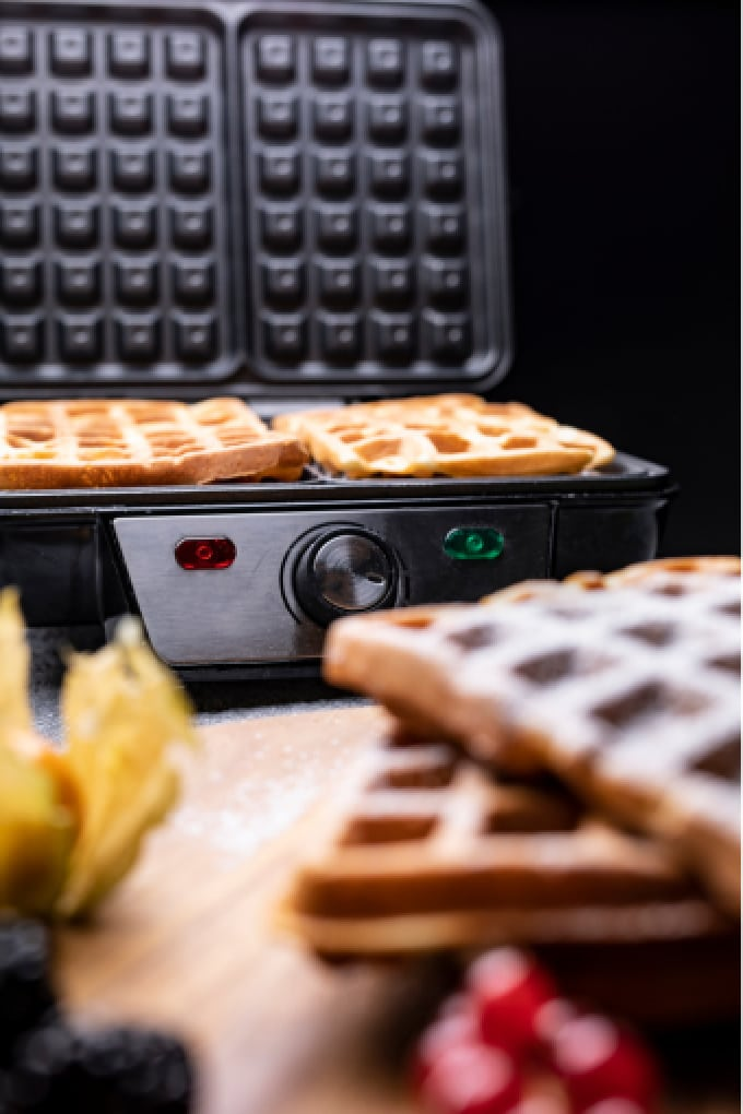 Waffle maker being used to make waffles.