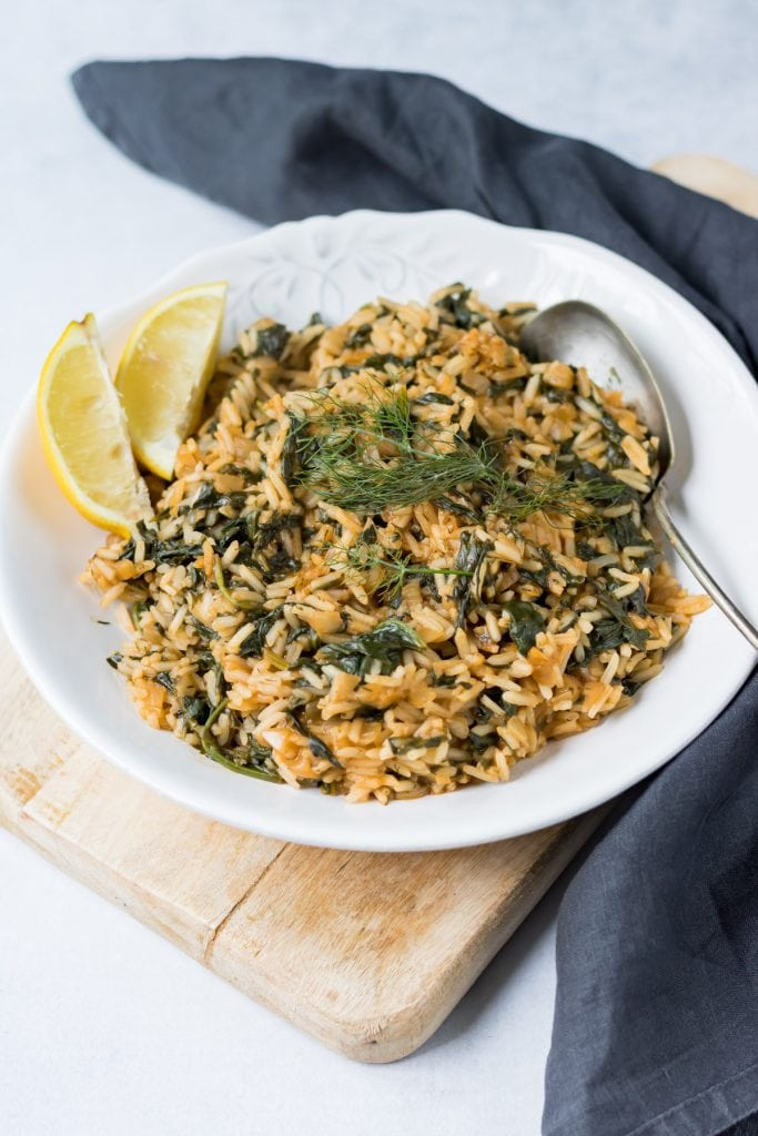 Plate of Greek Spinach Rice with napkin and serving spoon.