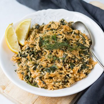 Dish of spinach rice with lemon wedges on the side.