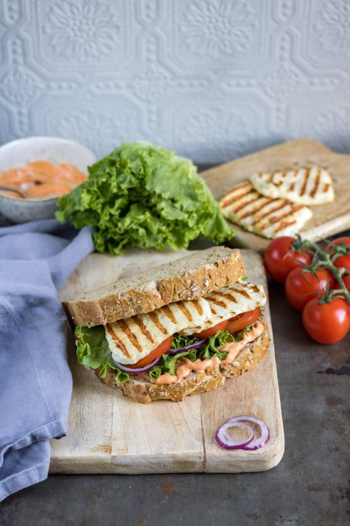 Table with a sandwich on a wooden board with lettuce, tomatoes and onion around it.