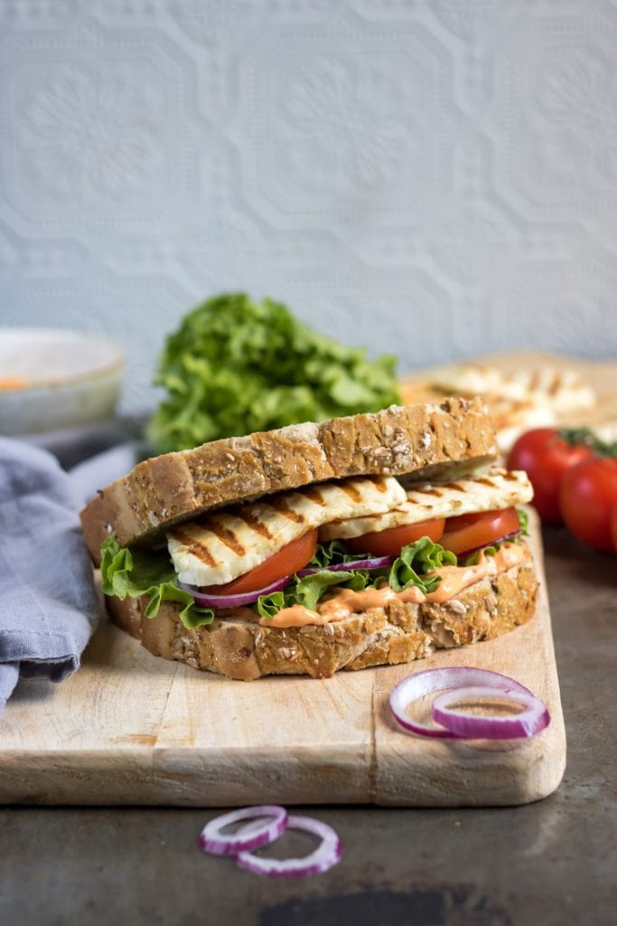 Close up of sandwich with halloumi, tomatoes, lettuce and sriracha mayo on a wooden board.