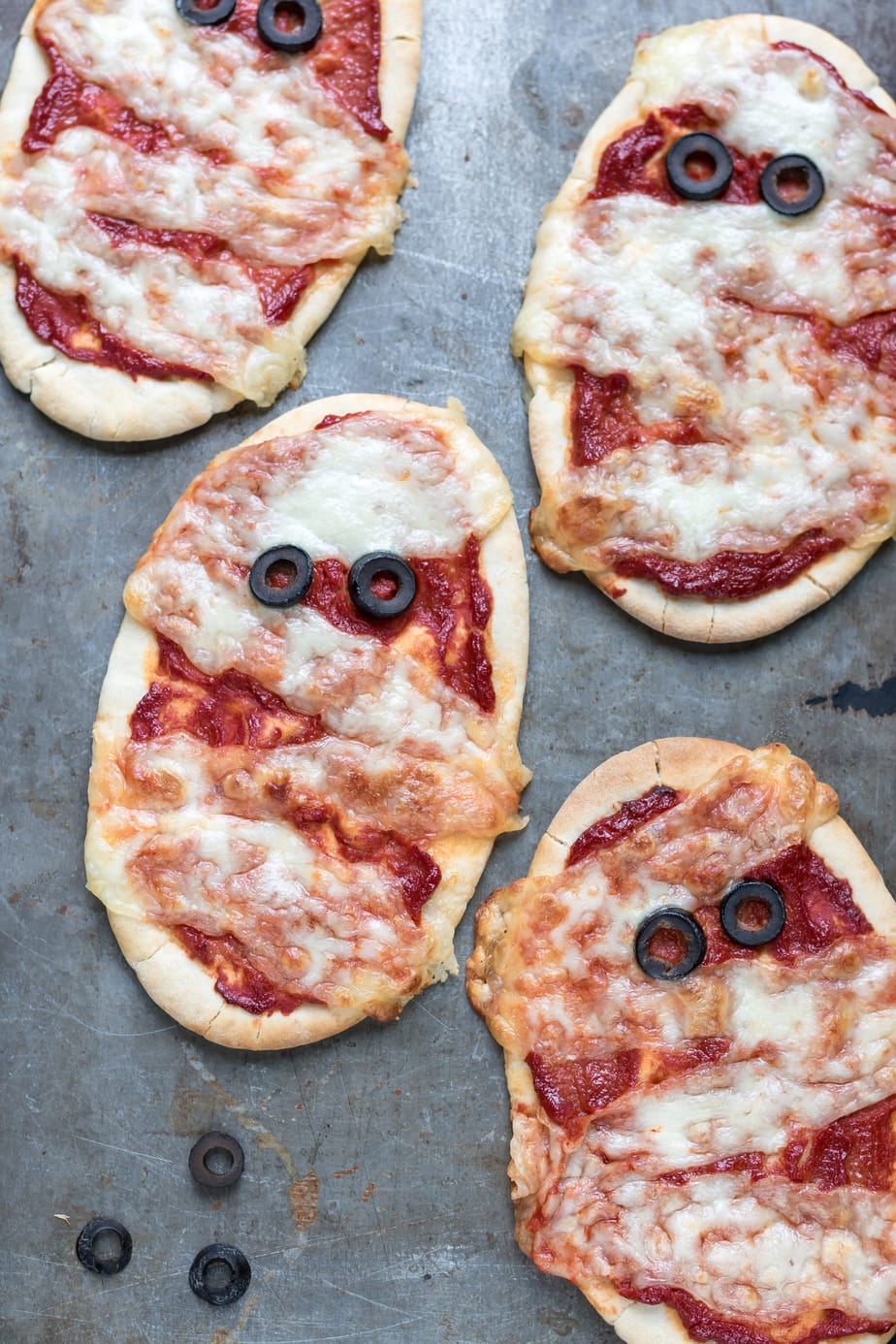 Close up of individual pita pizzas that look like Halloween mummies.