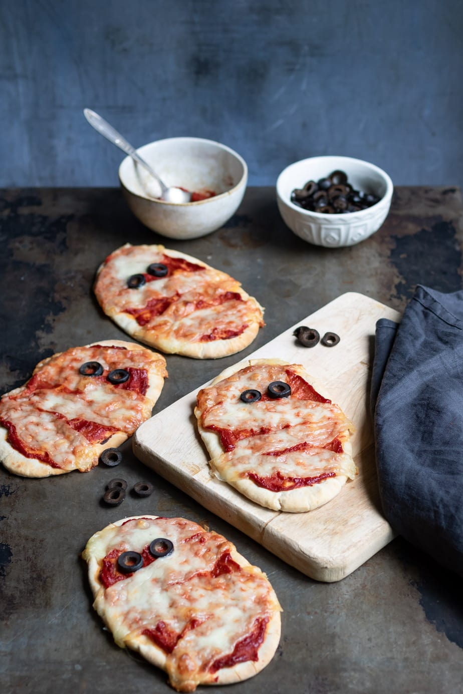 Pita pizzas with cheese and olives to look like Halloween Mummies.