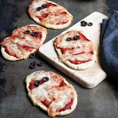 Pita pizzas decorated like Halloween mummys on a table and wooden board.