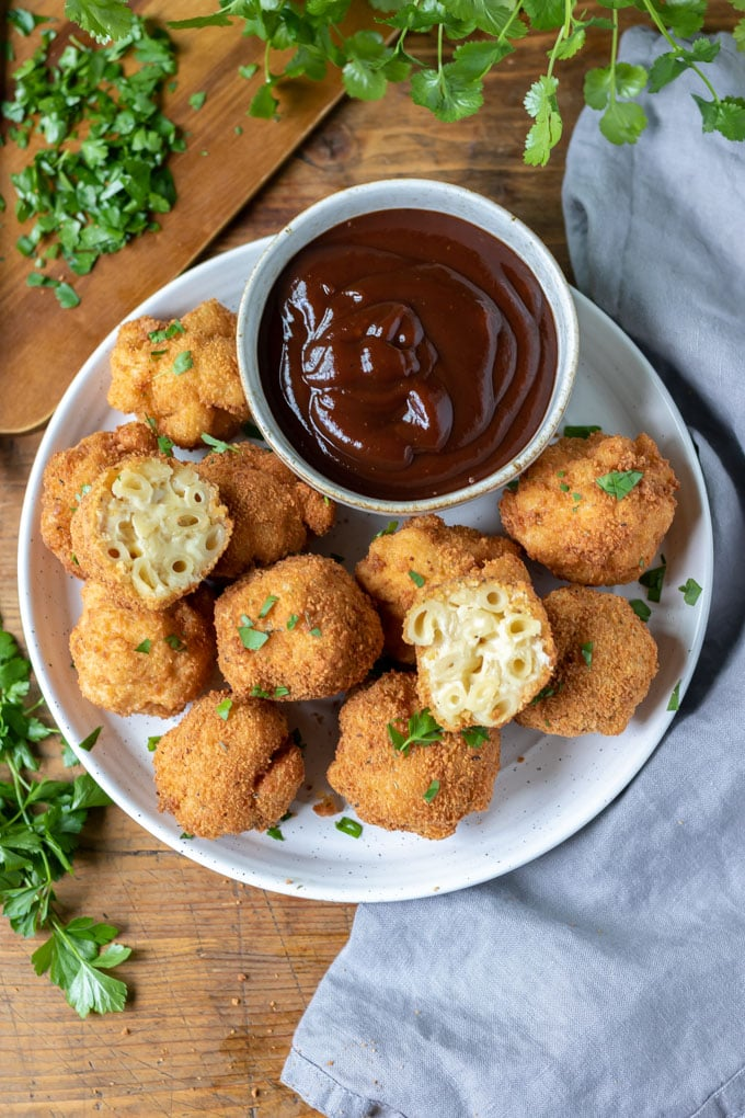Plate of macaroni cheese balls, with bbq dip and two balls cut open.