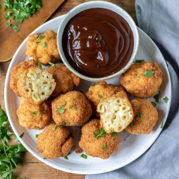 Plate of fried macaroni and cheese balls with bowl of barbecue sauce.