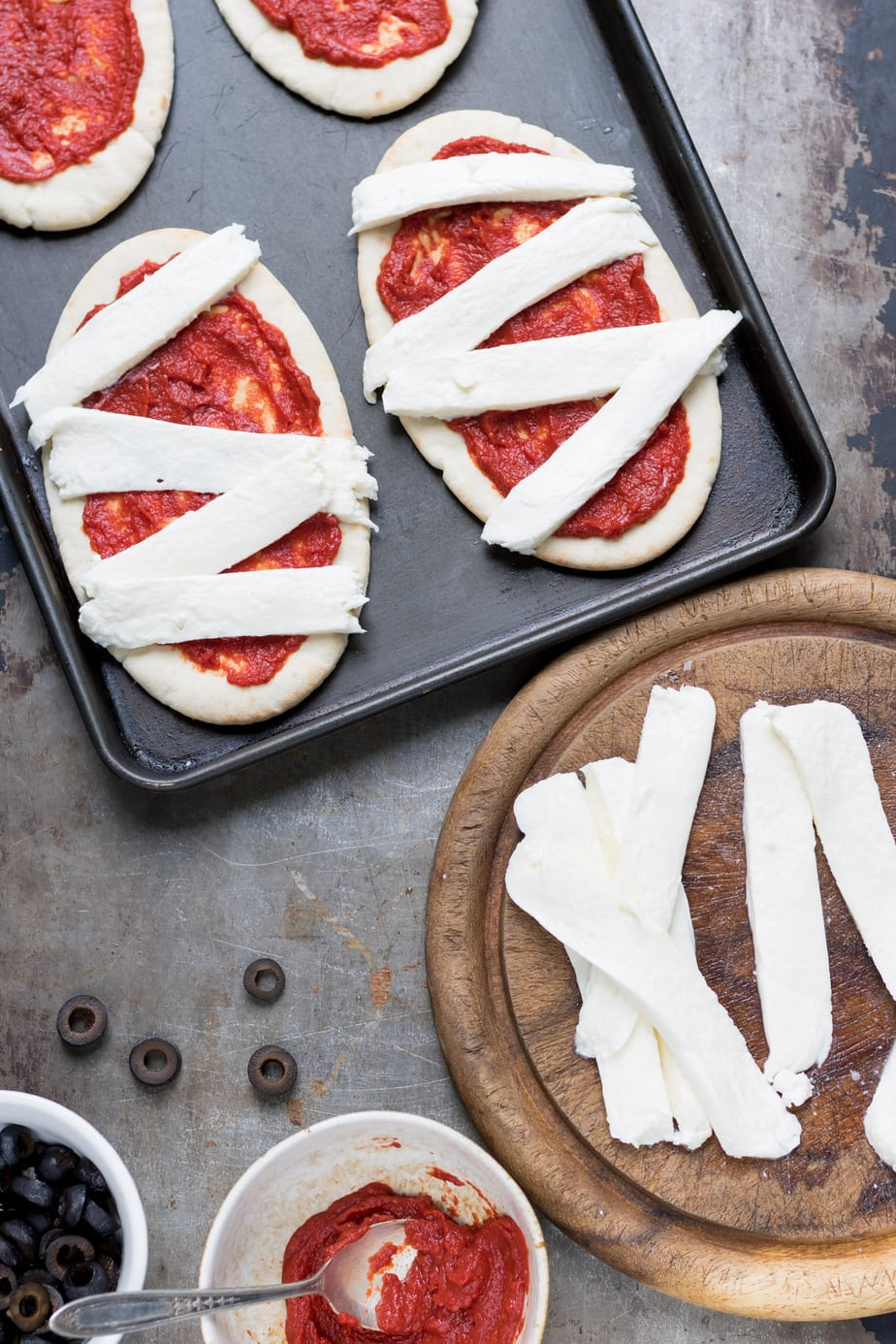 Pita breads with pizza sauce and strips of mozzarella cheese.