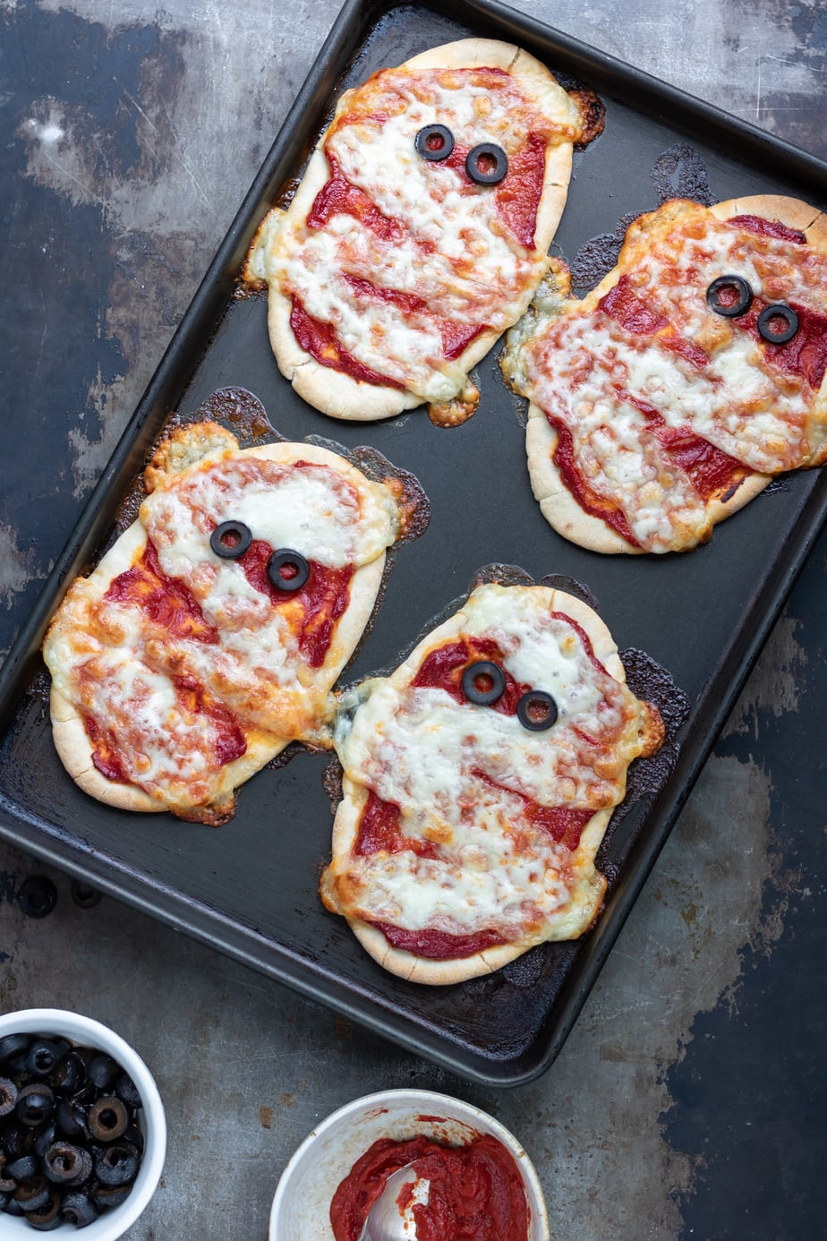 Baking sheet with cooked Halloween mummy pita pizzas.
