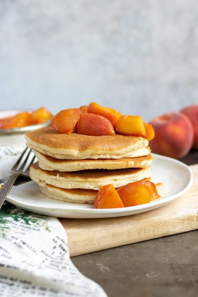Stack of pancakes topped with peach compote.
