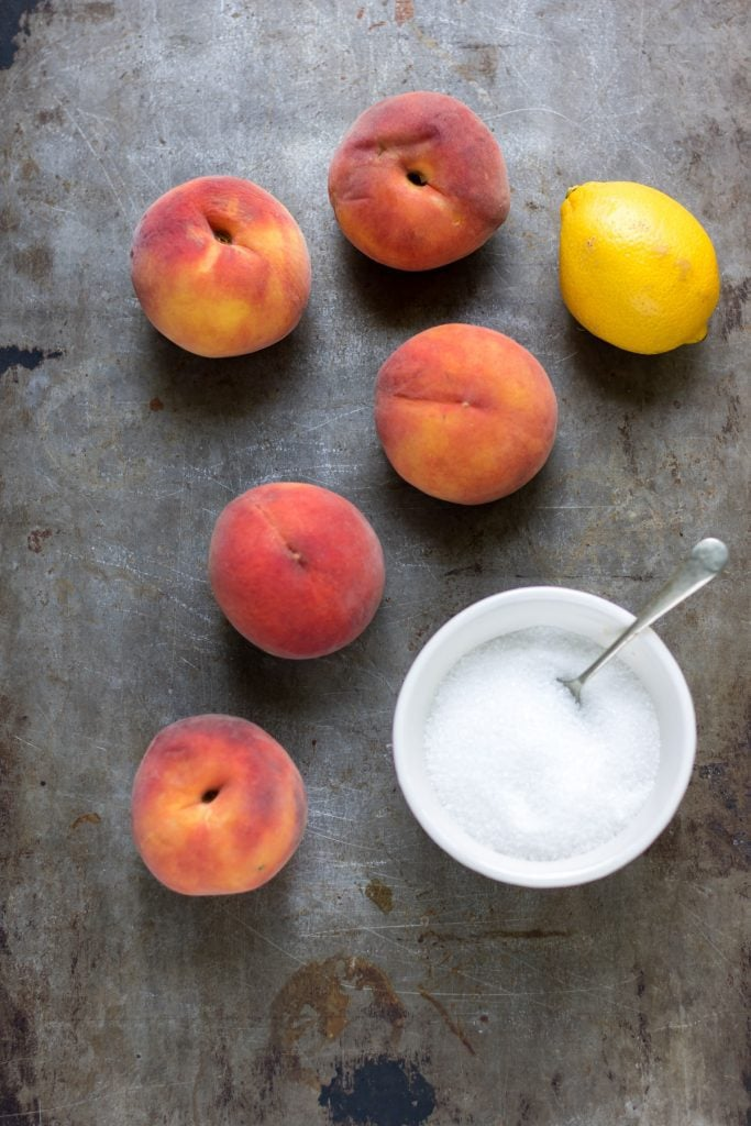 Peaches, lemon and sugar on a table.