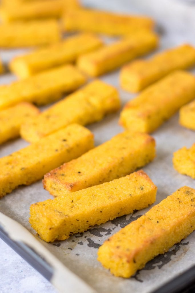 Close up of polenta chips on a baking tray.