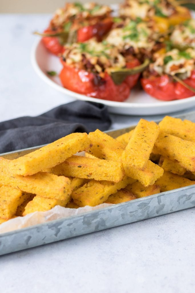 Tray of stacked polenta chips in front of a plate of stuffed peppers.