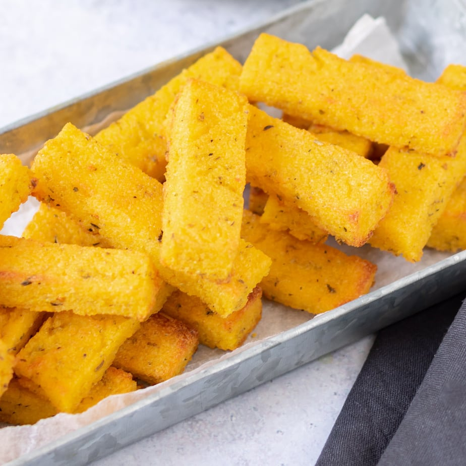Stack of polenta fries in metal tray.