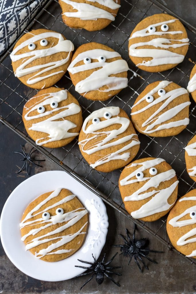 Cooling rack with pumpkin cookies drizzled with icing to look like Halloween mummies with candy eyes.