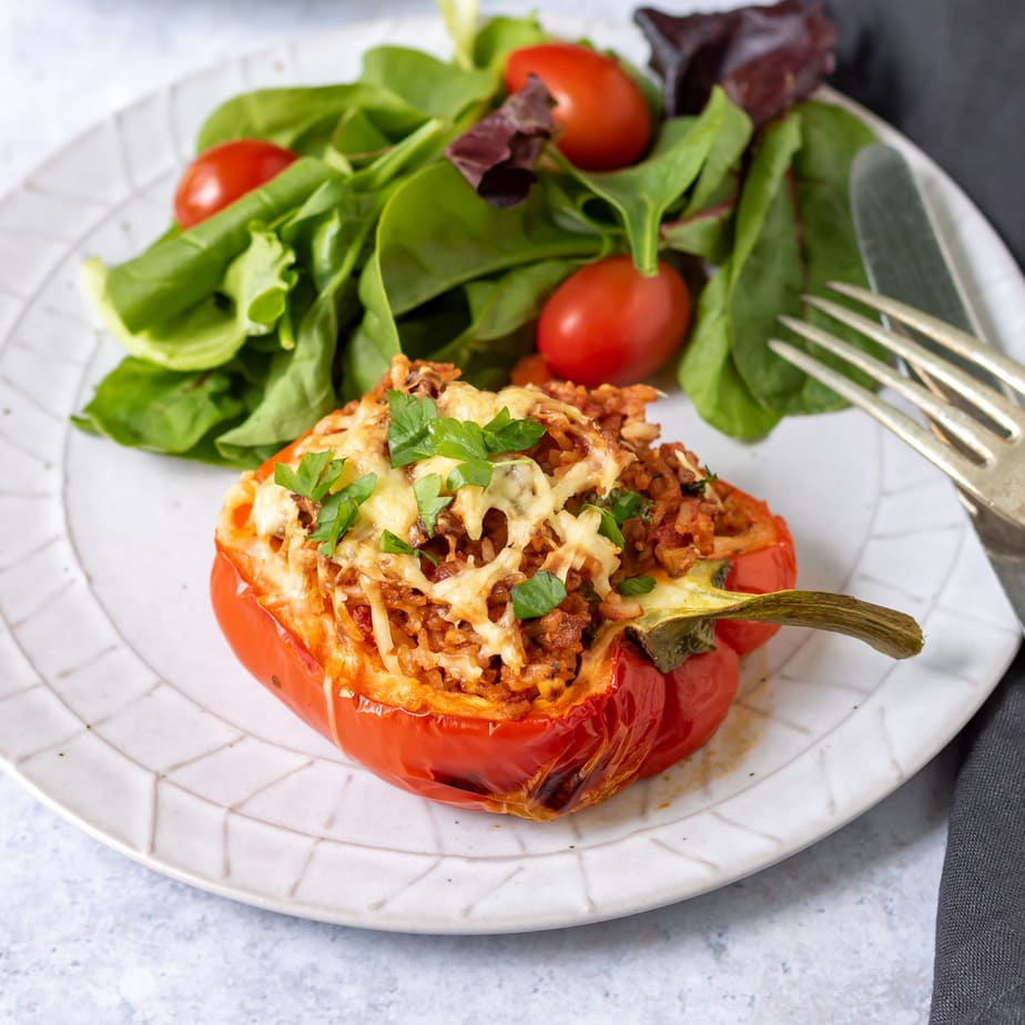Vegan stuffed pepper on a plate with salad.