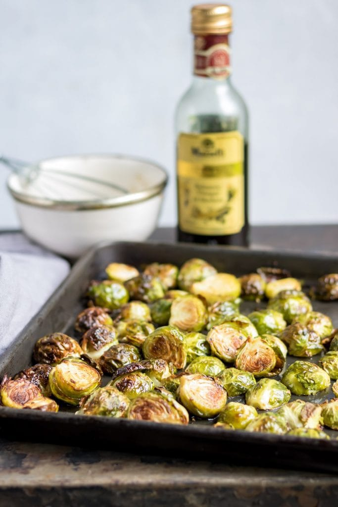Tray of roasted sprouts in front of bottle of balsamic vinegar.