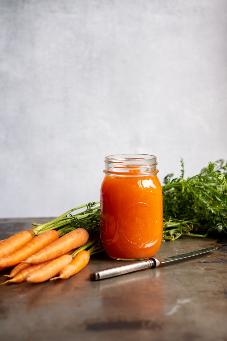 A jar of jam in front of a bunch of carrots.