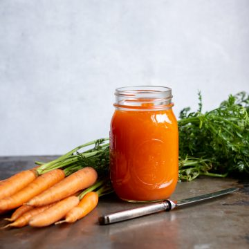 A jar of carrot jam next to a knife and carrots.