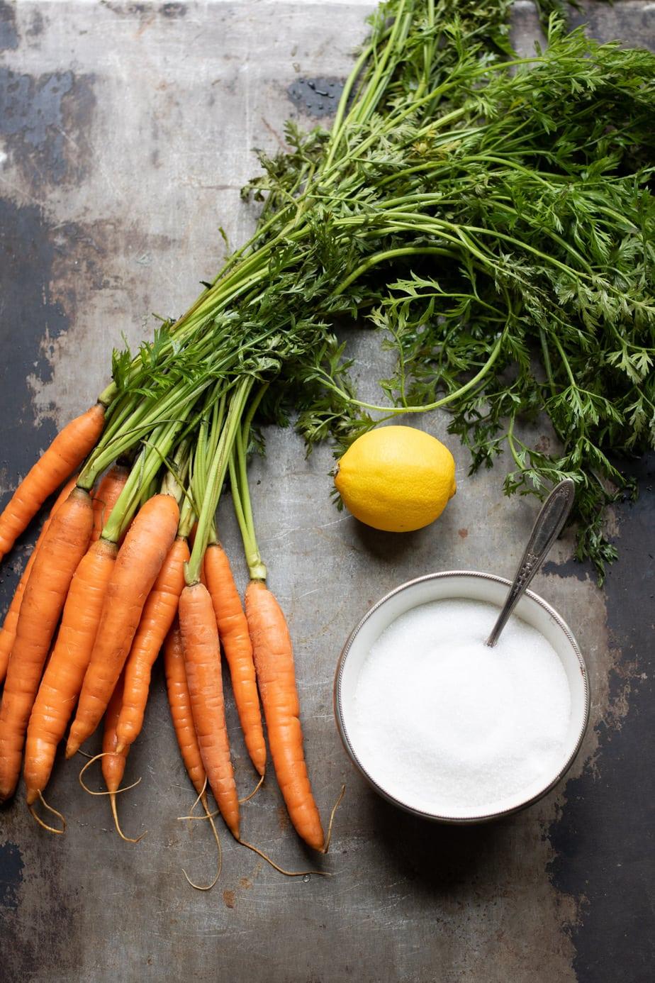 Carrots, lemon and sugar on a table.