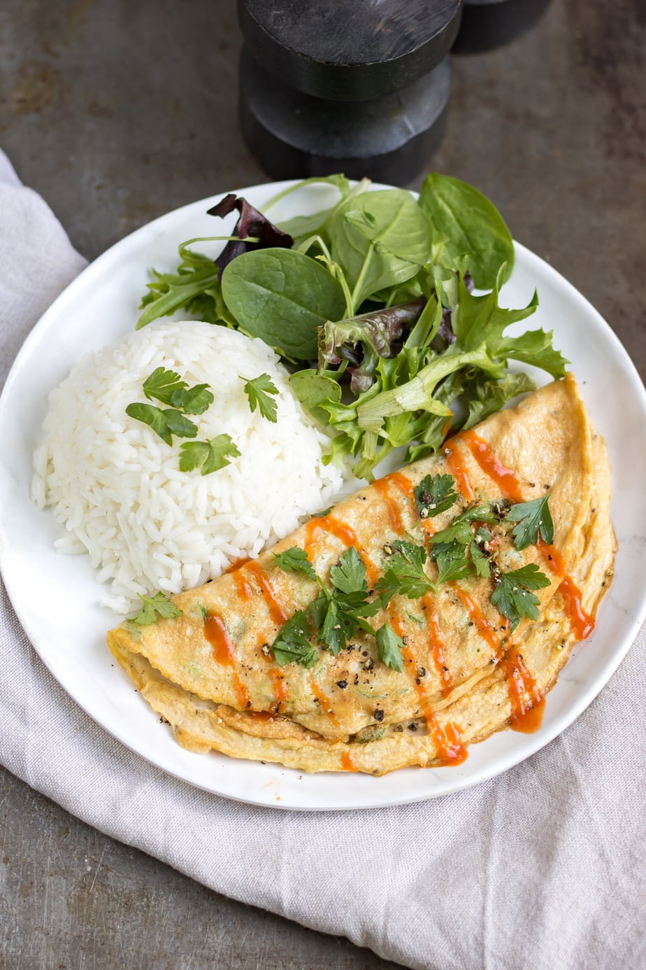 Plate with omelette, rice and salad.