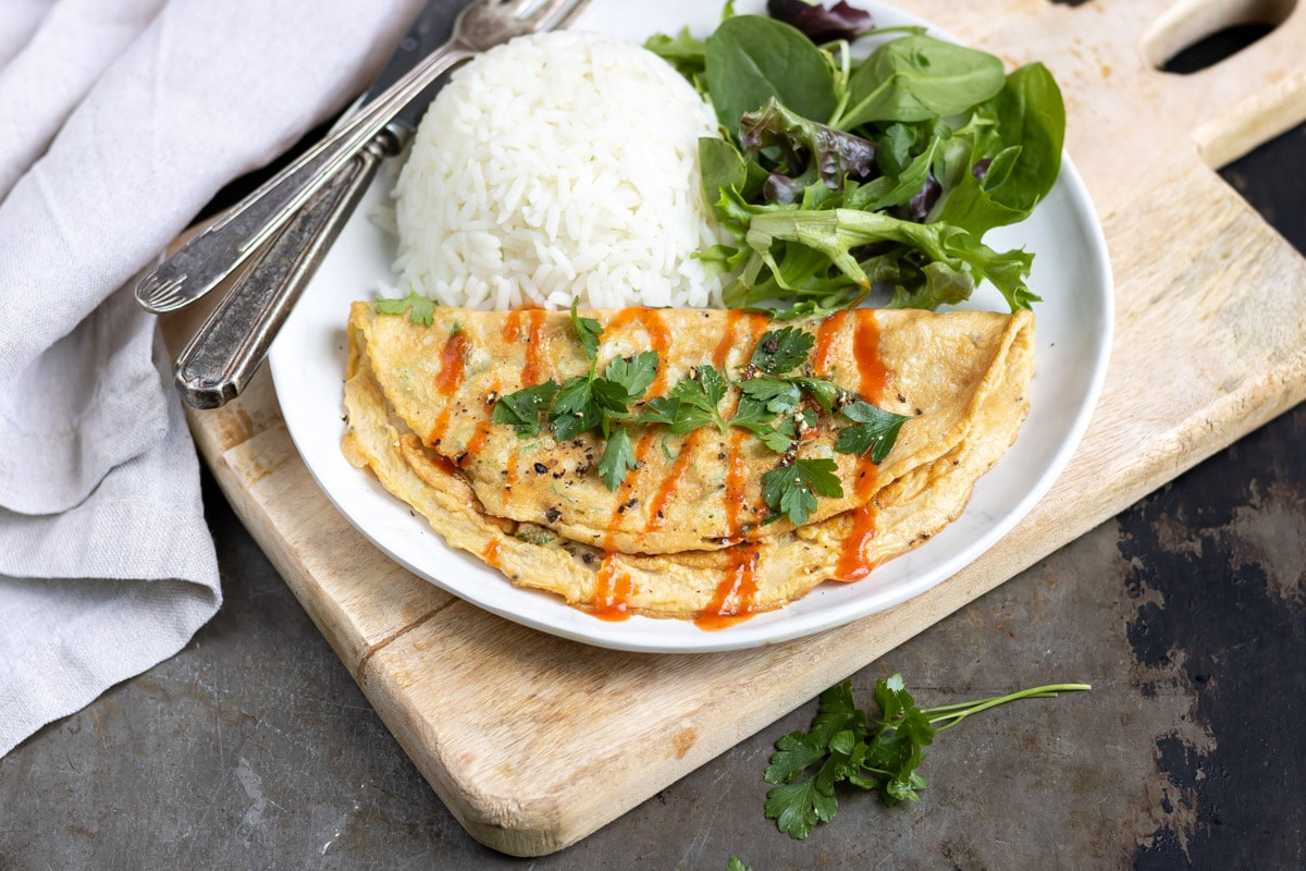 Plate on a board, with omelet, rice and lettuce.